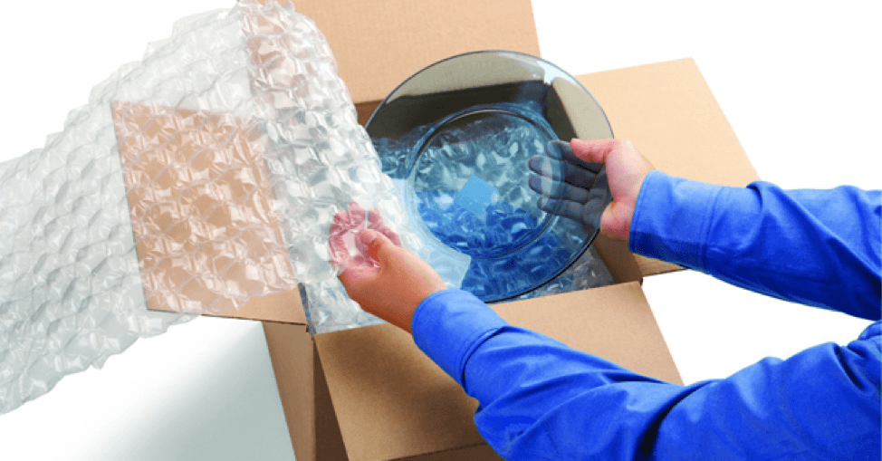 Moving valuable items - person packing glassware